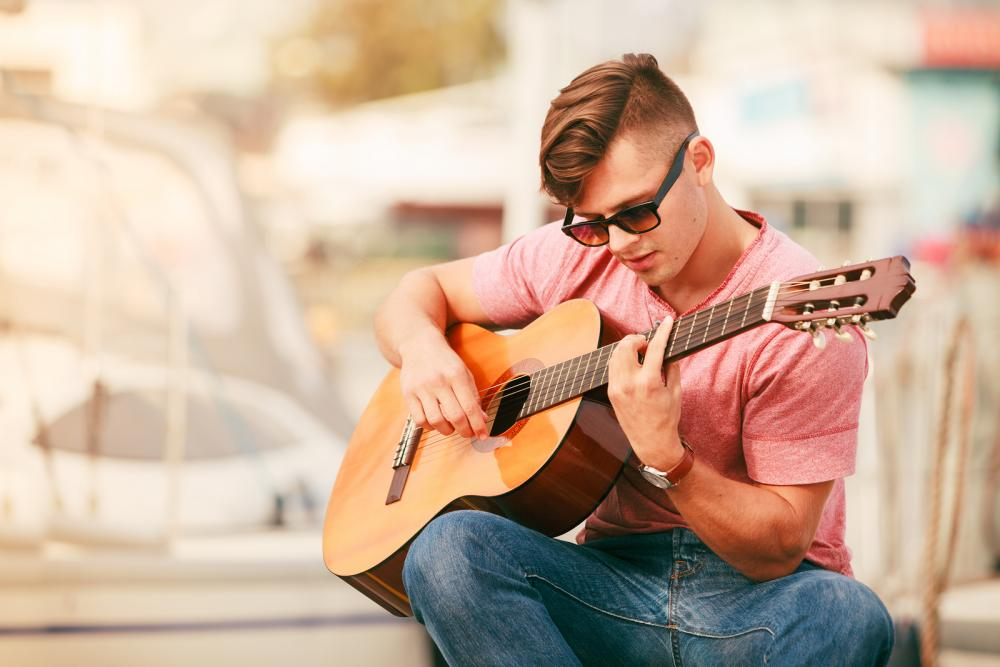 Man with prescription sunglasses and guitar from Plano Otometrist